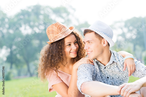 couple lying on the grass in the summer park