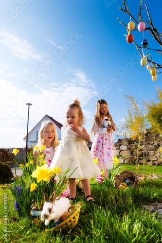 canvas print picture Kinder auf Ostereiersuche mit Osterhase an Ostern