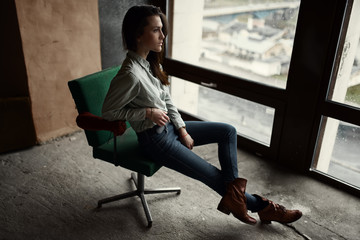 Fashion beautiful brunette sitting on an old chair