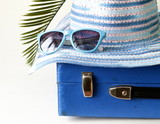 old fashioned blue suitcase for travel and beach hat
