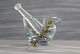 Fresh rosemary herb in glass mortar with pestle