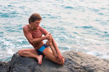 Young man doing yoga exercise wild stone sea beach.