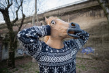 young hipster man horse mask