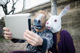 young hipster cuople horse and rabbit mask using tablet