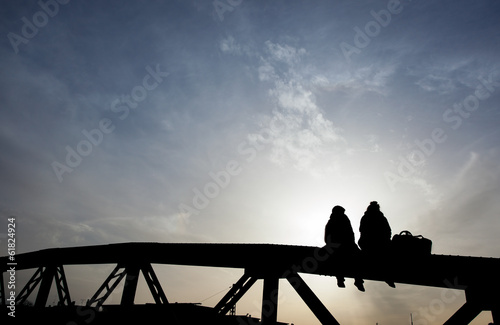silhouette of couple sitting on bridge