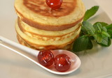 Pancakes with candied cherries and mint leaves