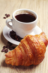 Coffee cup with a croissant