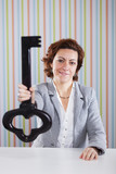 Businesswoman holding a giant key