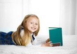 happy cute blonde haired school girl reading a book looking at c