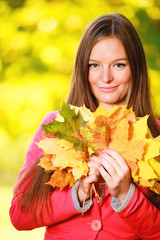 Fall season. Portrait girl woman with bunch of autumnal leaves
