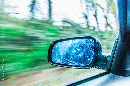 Leinwandbild Motiv Car on the road rear view mirror motion blur background