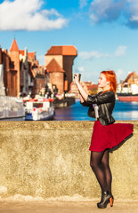 traveler woman red hair girl with camera old town Gdansk