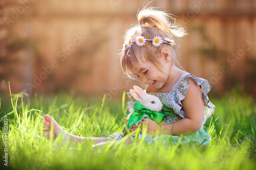 canvas print picture Cute little girl with a bunny rabbit has a easter at green grass