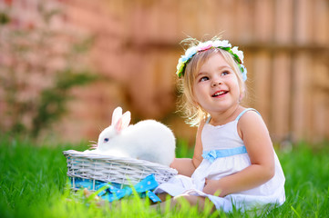 Cute little girl with a bunny rabbit has a easter at green grass