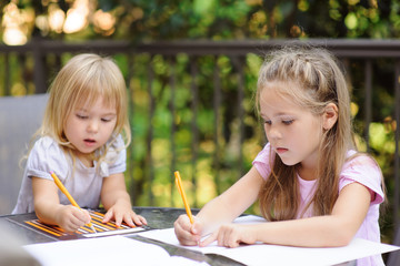 two little kid making school homework