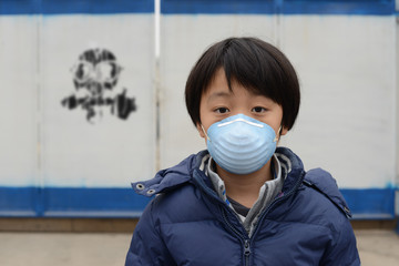 Asian boy wearing mouth mask against air pollution (Beijing)