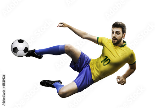 Brazilian soccer player kicks the ball on white background