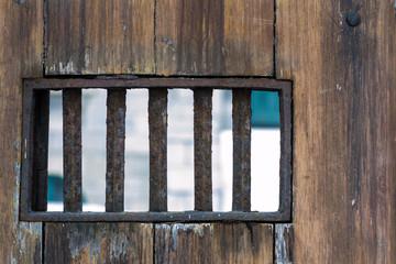 Small window wth bars on wooden door