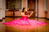 Beautiful woman playing violin with big dress