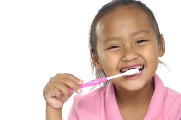 Little girl brushing teeth with white toothbrush