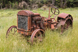 abandoned tractor in grass field
