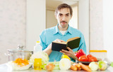 Portrait of man with cookbook in domestic kitchen