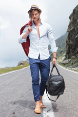 young man walking with bag on the road