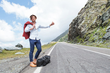 young fashion man hitchhikes with joy