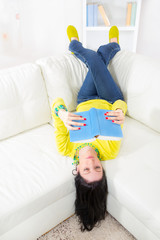 A young woman lying on her back on the sofa reading book
