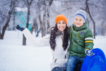 happy mother and son are playing with snow