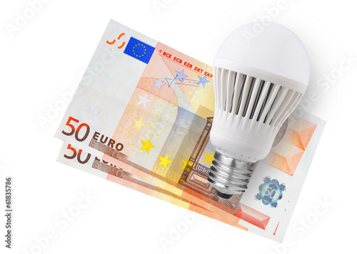 LED bulb over euro bills on white background