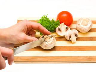 Cutted mushrooms, tomato and parsley on a hardboard