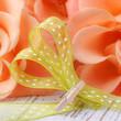 Herz aus Schleifenband vor Rosenblüten