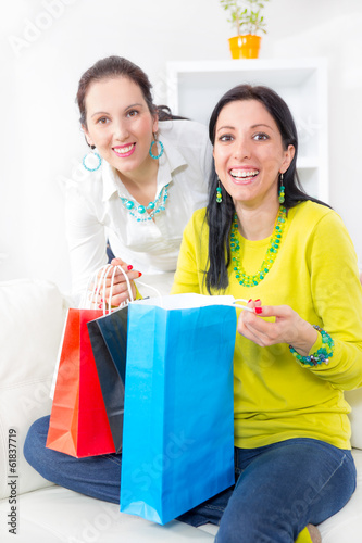 Two beautiful women friends at home looking in shopping bags