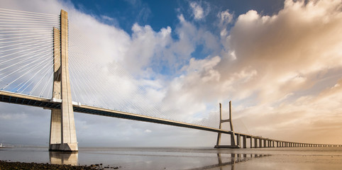 Vasco da Gama Bridge over the Tagus river at sunrise with cloudy