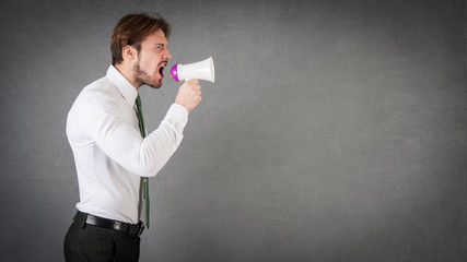 Man shouting with megaphone against grunge background.