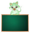 A green cat leaning above the blackboard