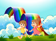 Happy kids playing at the hilltop with a rainbow