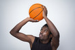 Basketball player throwing the ball against gray background