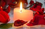 a burning candle in rose petals