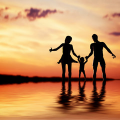 Happy family walking together hand in hand at sunset