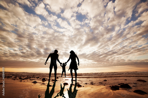 Happy family together hand in hand on the beach at sunset.