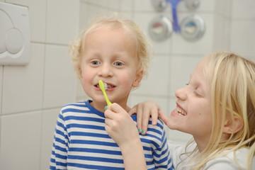 Schwester putzt kleinem Bruder die Zähne