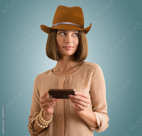 Portrait of a cheerful young woman wearing hat using her smartph