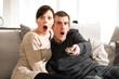 Junges Paar mit Fernbedienung, entsetzt, Horror, Angst
