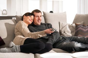 Junges Paar auf Sofa mit Fernbedienung