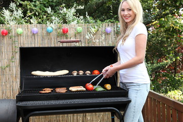 Beautiful blond woman barbecuing on a patio