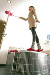 Junge Frau putzt  Badewanne, Wannenrand