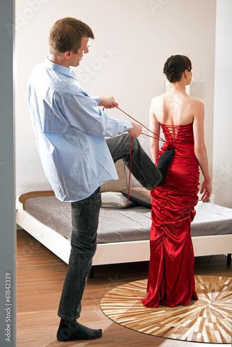 Mann hilft Frau beim Ankleiden, Anziehen