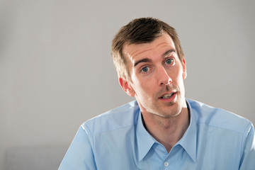 Mimik, Gesicht, junger Mann, blaues Hemd, kurze, dunkle Haare